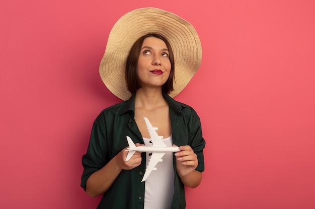 Zadowolona ładna kobieta w kapeluszu plażowym trzyma model samolotu i patrzy w górę na białym tle na różowej ścianie