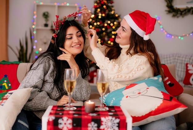 Zadowolona ładna młoda dziewczyna w czapce świętego mikołaja trzyma i patrzy na swojego przyjaciela ostrokrzewowy wieniec siedzący na fotelach i cieszący się świątecznym czasem w domu