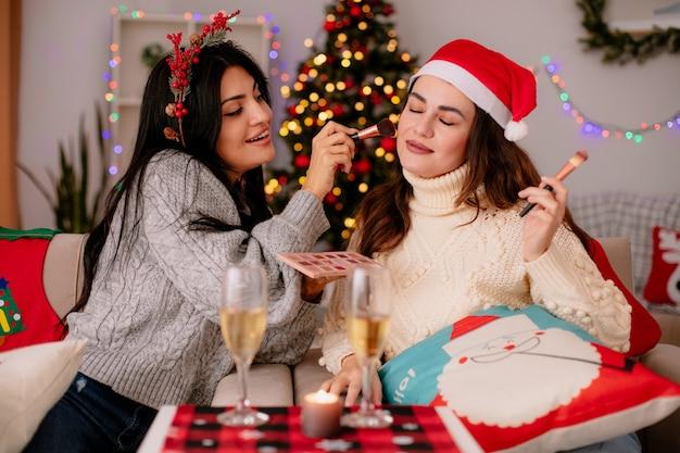 Zadowolona ładna młoda dziewczyna z ostrokrzewem robi makijaż przyjacielowi pędzlem do pudru, siedząc na fotelach i ciesząc się świątecznym czasem w domu