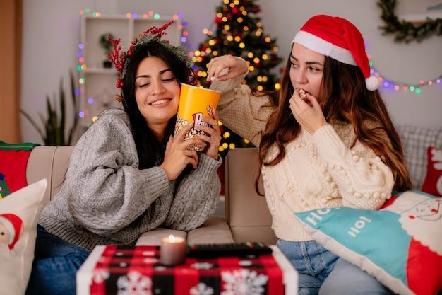 Zadowolona ładna młoda dziewczyna z ostrokrzewowym wieńcem trzyma wiadro popcornu, a jej przyjaciółka w czapce mikołaja je popcorn siedząc na fotelu i ciesząc się świątecznym czasem w domu