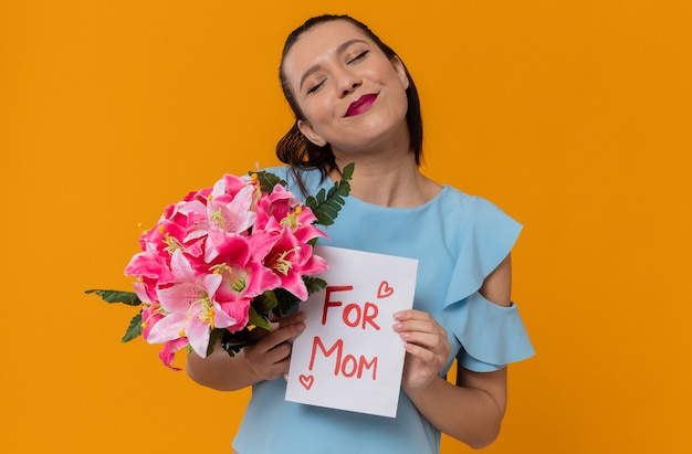 Zadowolona ładna młoda kobieta trzyma bukiet kwiatów i list od dziecka