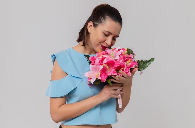 Zadowolona ładna młoda kobieta trzyma i wącha bukiet kwiatów