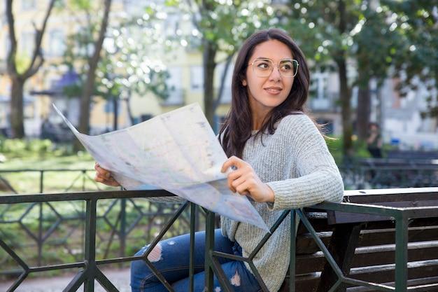 Zadowolona ładna młoda kobieta używa papierową mapę na ławce outdoors