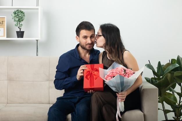 Zadowolona ładna młoda kobieta w okularach optycznych trzymająca bukiet kwiatów i całująca przystojnego mężczyznę trzymającego pudełko siedzące na kanapie w salonie w marcowy międzynarodowy dzień kobiet