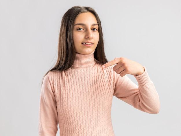 Zadowolona ładna nastolatka wskazująca na przestrzeń przed nią na białym tle na białej ścianie