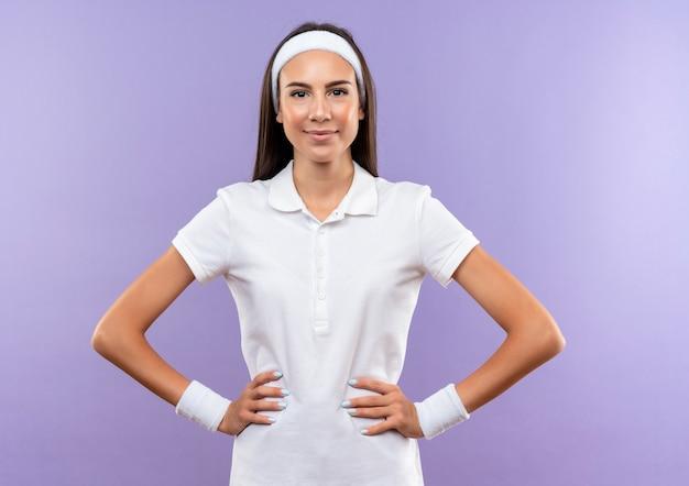 Zadowolona ładna sportowa dziewczyna z opaską na głowę i nadgarstkiem z rękami w talii odizolowana na fioletowym obszarze