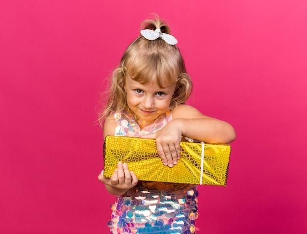 Zadowolona mała blondynka trzyma pudełko na prezent na różowej ścianie z miejscem na kopię copy