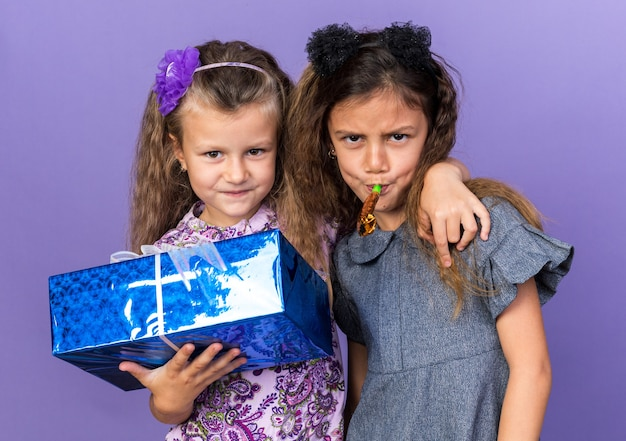 Zadowolona mała blondynka trzymająca pudełko i stojąca z radosną małą brunetką dmuchającą w gwizdek na fioletowej ścianie z kopią miejsca