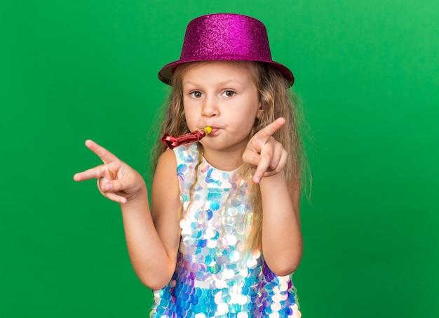 Zadowolona mała blondynka w fioletowym kapeluszu imprezowym dmuchający gwizdek i gestykulujący znak zwycięstwa na zielonej ścianie z miejscem na kopię