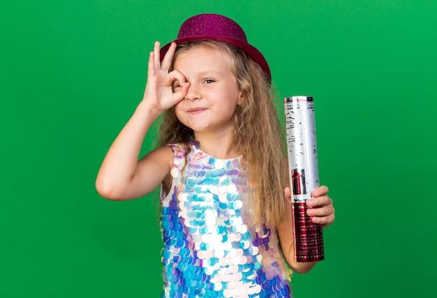 Zadowolona mała blondynka w fioletowym kapeluszu imprezowym trzymająca armatę konfetti i patrząca przez palce odizolowane na zielonej ścianie z miejscem na kopię