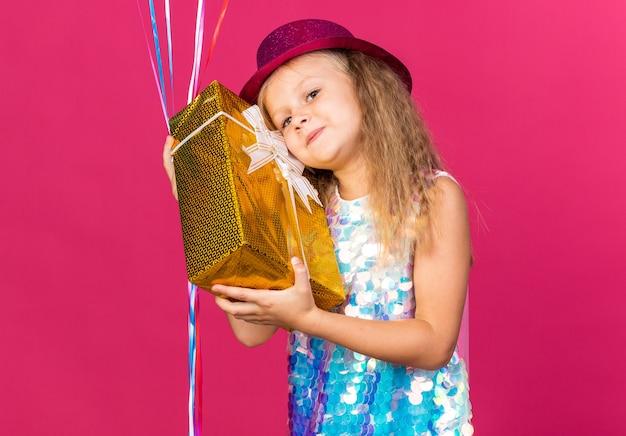 Zadowolona mała blondynka w fioletowym kapeluszu imprezowym trzymająca balony z helem i pudełko na prezenty odizolowane na różowej ścianie z miejscem na kopię