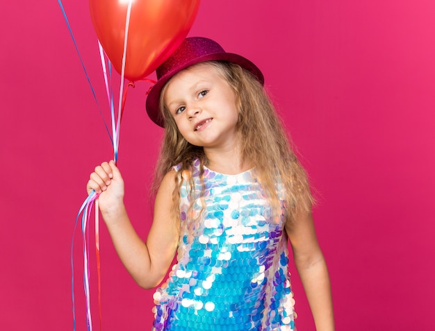 Zadowolona mała blondynka w fioletowym kapeluszu imprezowym trzymająca balony z helem odizolowane na różowej ścianie z miejscem na kopię