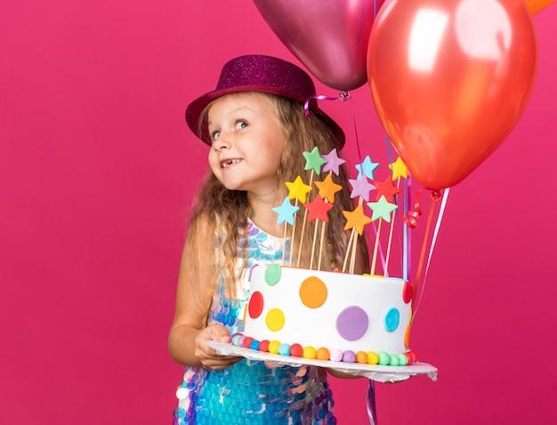 Zadowolona mała blondynka w fioletowym kapeluszu z balonów z helem i tortem urodzinowym na białym tle na różowej ścianie z miejsca na kopię