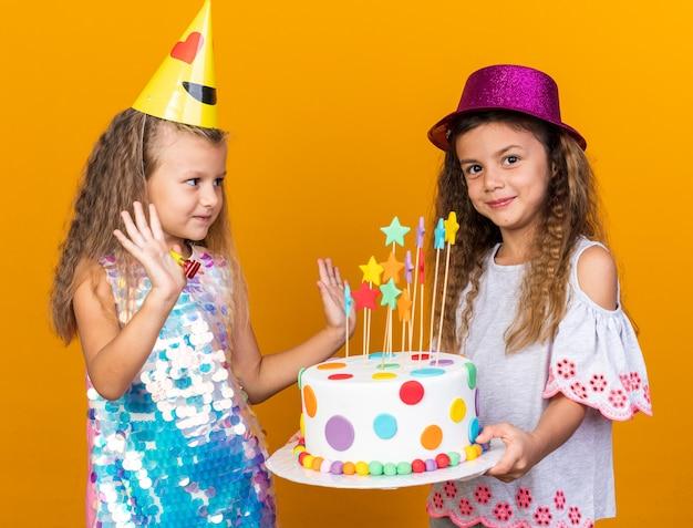 Zadowolona mała blondynka w imprezowej czapce stoi z uniesionymi rękami i patrzy na małą kaukaską dziewczynkę w fioletowym kapeluszu trzymającym tort urodzinowy odizolowaną na pomarańczowej ścianie z kopią miejsca
