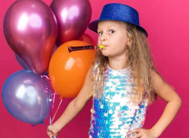 Zadowolona mała blondynka w niebieskim kapeluszu imprezowym trzymająca balony z helem i gwizdek na różowej ścianie z miejscem na kopię