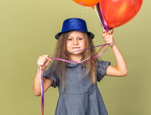 Zadowolona mała blondynka w niebieskim kapeluszu imprezowym trzymająca balony z helem odizolowane na oliwkowozielonej ścianie z miejscem na kopię