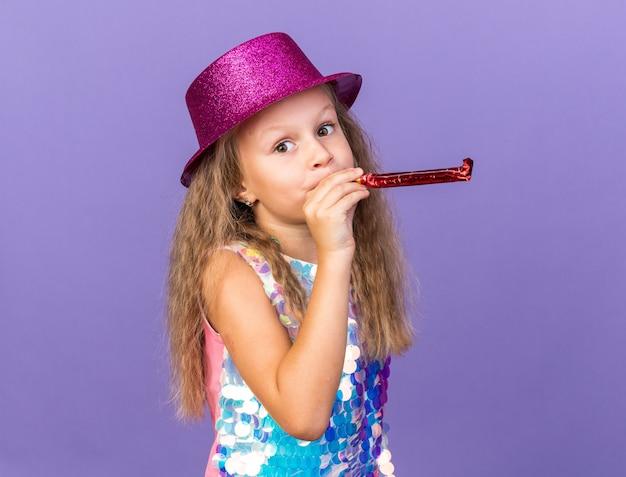 Zadowolona mała blondynka z fioletowym kapeluszem imprezowym wieje gwizdek i szuka odizolowanej na fioletowej ścianie z miejsca na kopię