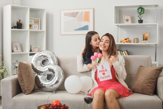 Zadowolona mała dziewczynka stojąca za sofą trzymająca kwiaty z kartką z życzeniami przytulająca i całująca matkę na kanapie w szczęśliwy dzień kobiet w salonie