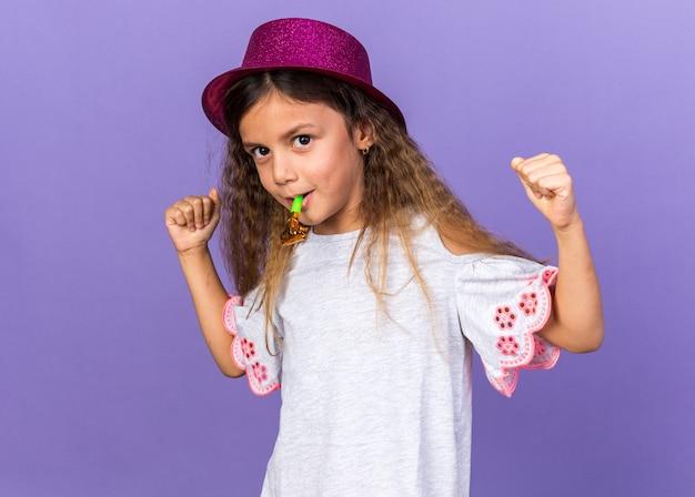 Zadowolona mała kaukaska dziewczyna w fioletowym kapeluszu imprezowym dmuchająca w gwizdek i trzymająca pięści odizolowane na fioletowej ścianie z miejscem na kopię