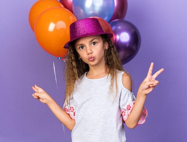 Zadowolona mała kaukaska dziewczyna w fioletowym kapeluszu imprezowym gestem znaku zwycięstwa stojąca przed balonami z helem odizolowanych na fioletowej ścianie z kopią miejsca