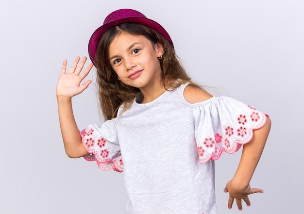 Zadowolona mała kaukaska dziewczyna w fioletowym kapeluszu imprezowym trzymająca otwarte ręce na białej ścianie z miejscem na kopię