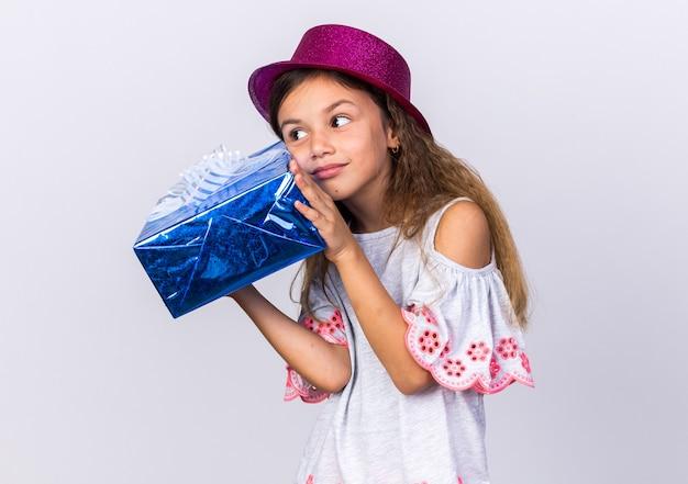 Zadowolona mała kaukaska dziewczyna w fioletowym kapeluszu imprezowym trzymająca pudełko na białym tle na białej ścianie z miejscem na kopię