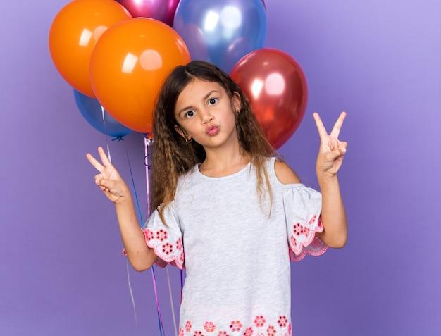 Zadowolona mała kaukaska dziewczynka gestykulująca znak zwycięstwa stojąca przed balonami z helem odizolowanych na fioletowej ścianie z kopią przestrzeni