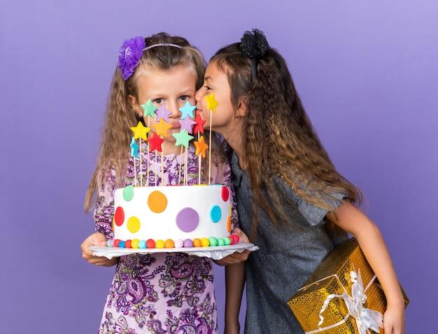 Zadowolona mała kaukaska dziewczynka trzymająca pudełko i całująca smutną małą blondynkę trzymającą tort urodzinowy na fioletowej ścianie z miejscem na kopię