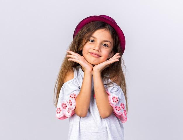 Zadowolona mała kaukaska dziewczynka w fioletowym, imprezowym kapeluszu, kładąca ręce na brodzie na białej ścianie z miejscem na kopię