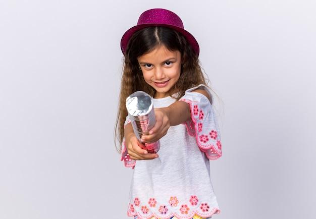 Zadowolona mała kaukaska dziewczynka w fioletowym kapeluszu imprezowym trzymająca armatę konfetti na białej ścianie z miejscem na kopię