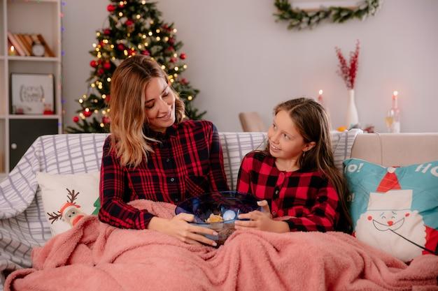 Zadowolona mama i córka trzymają miskę chipsów przykrytą kocem, siedząc na kanapie i ciesząc się świętami bożego narodzenia w domu