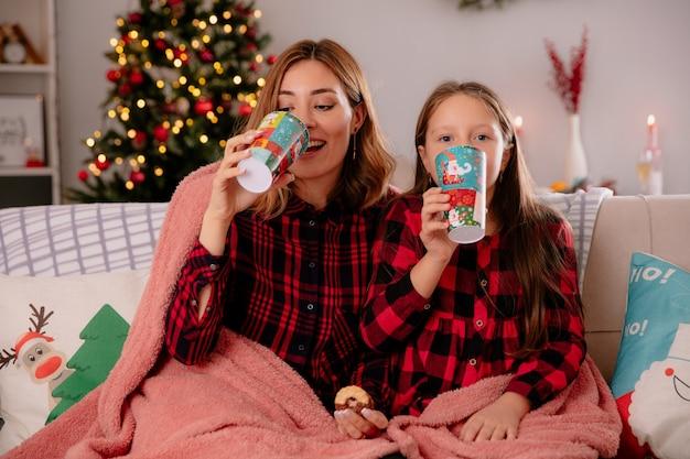 Zadowolona mama i córka trzymające papierowy kubek i ciasteczka siedzące na kanapie przykrytej kocem i cieszące się świętami bożego narodzenia w domu