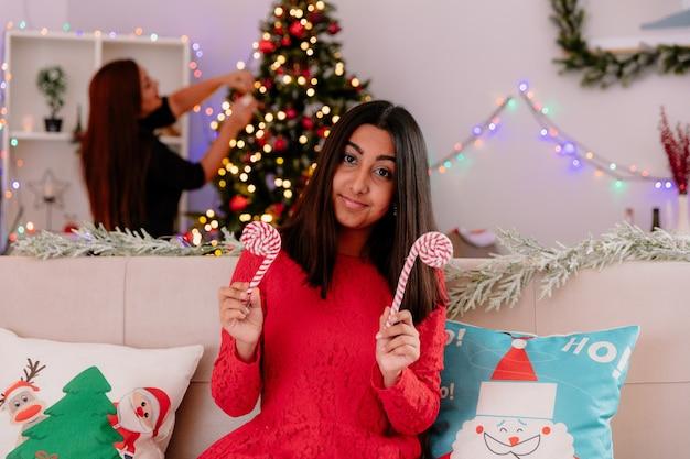 Zadowolona mama ozdabia choinkę, a jej córka trzyma cukierkową laskę siedzącą na kanapie, ciesząc się świątecznymi chwilami w domu