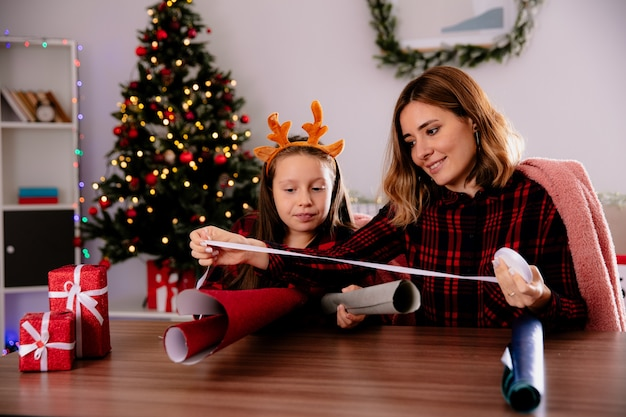 Zadowolona mama uczy córkę zawijać prezenty w kolorowe papiery trzymając taśmę siedząc przy stole ciesząc się świętami w domu