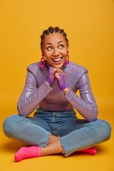Zadowolona, marzycielska młoda afroamerykańska kobieta skoncentrowana powyżej, trzyma ręce pod brodą, siedzi w pozie lotosu na żółtej ścianie, ubrana w stylowe ubrania i sportowe rękawiczki, uśmiecha się szeroko