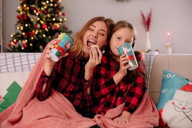 Zadowolona matka i córka trzymające papierowe kubki i jedzące ciastka siedzące na kanapie przykrytej kocem i cieszące się świętami bożego narodzenia w domu