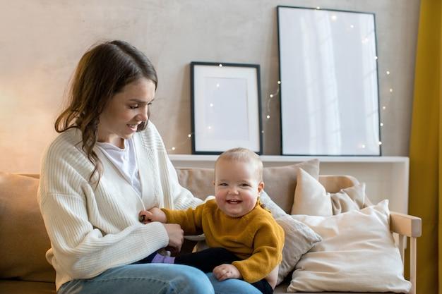 Zadowolona matka z berbeciem na kanapie