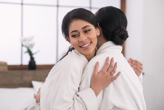Zadowolona miła pozytywna kobieta uśmiechając się przytulając swoją dziewczynę