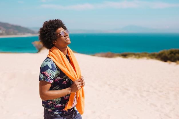 Zadowolona młoda amerykanin afrykańskiego pochodzenia męska pozycja na plaży