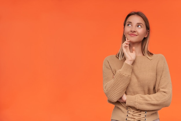 Zadowolona młoda atrakcyjna blondynka z krótką fryzurą, uśmiechnięta delikatnie, patrząc w górę i dotykająca twarzy uniesioną ręką, odizolowana na pomarańczowej ścianie