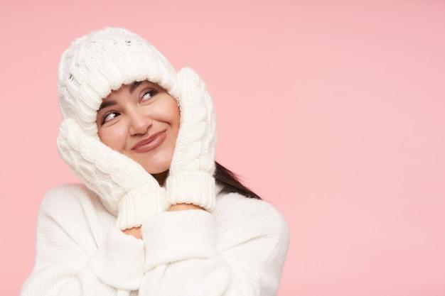 Zadowolona młoda atrakcyjna brązowowłosa dama w białej dzianinowej czapce, trzymająca podniesione dłonie na policzkach, jednocześnie patrząc w górę z ładnym uśmiechem, pozująca na różowej ścianie