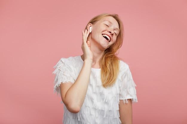 Zadowolona młoda atrakcyjna dama z lśniącymi włosami, ciesząca się ulubionym utworem muzycznym z zamkniętymi oczami i uśmiechnięta pozytywnie, trzymając podniesioną rękę na słuchawce, stojąc na różowym tle