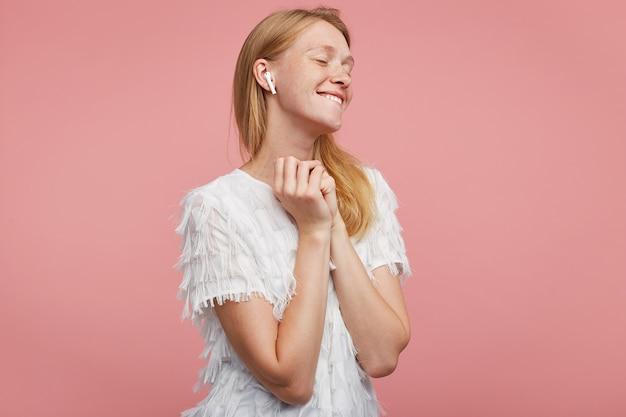 Zadowolona młoda atrakcyjna kobieta z lśniącymi włosami składającymi uniesione ręce i pozytywnie uśmiechająca się podczas słuchania ulubionego utworu muzycznego, stojąca na różowym tle