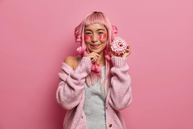 Zadowolona młoda azjatka lubi zabiegi kosmetyczne na skórę i aktywność fryzjerską