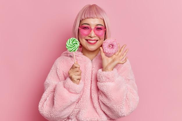 Zadowolona młoda azjatka z różowymi włosami bob, uśmiecha się delikatnie, trzyma lizaka i pysznego pączka