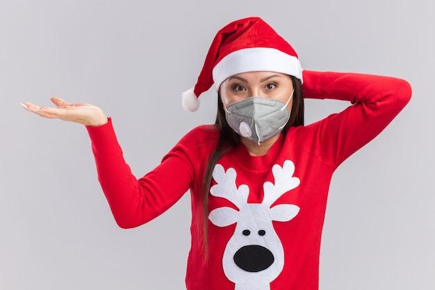 Zadowolona młoda azjatycka dziewczyna ubrana w świąteczny kapelusz ze swetrem i maską medyczną, kładąc dłoń na głowie na białym tle na białej ścianie