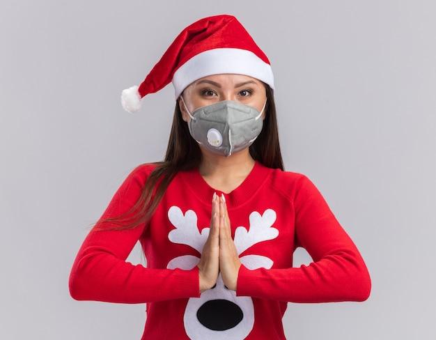 Zadowolona młoda azjatycka dziewczyna ubrana w świąteczny kapelusz ze swetrem i maską medyczną pokazując gest modlitwy na białym tle