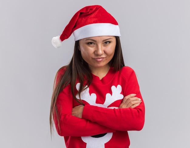 Zadowolona młoda azjatycka dziewczyna ubrana w świąteczny kapelusz ze swetrem krzyżującym ręce na białym tle