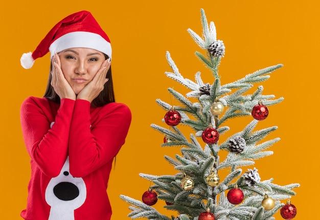 Zadowolona młoda azjatycka dziewczyna ubrana w świąteczny kapelusz ze swetrem stojąca w pobliżu choinki kładąc ręce na policzkach na białym tle na pomarańczowym tle