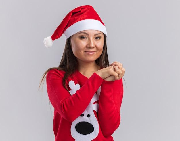 Zadowolona młoda azjatycka dziewczyna ubrana w świąteczny kapelusz ze swetrem, trzymając się za ręce razem na białym tle